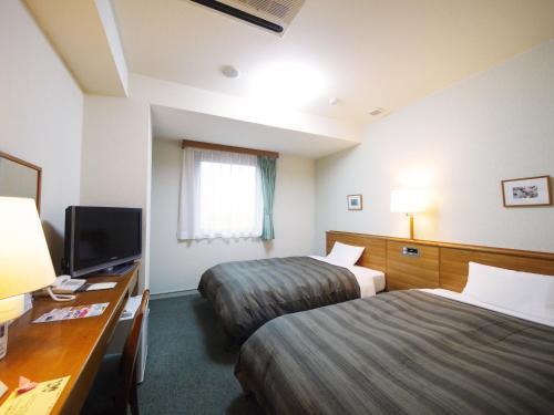 Un ou plusieurs lits dans un hébergement de l'établissement Hotel Route-Inn Kani