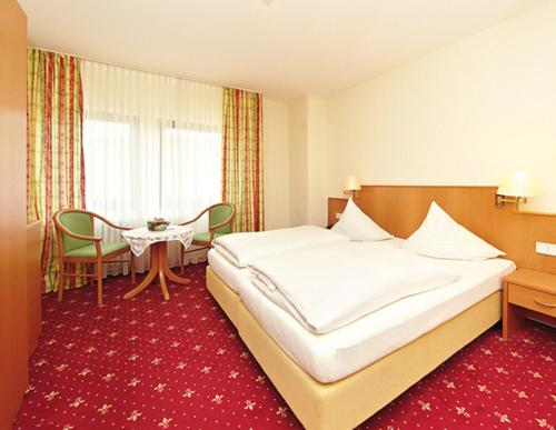 A bed or beds in a room at WeinBergHotel Nalbach