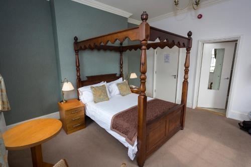 A bed or beds in a room at The Golf Hotel