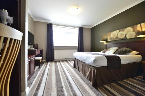 A bed or beds in a room at Birch Hotel