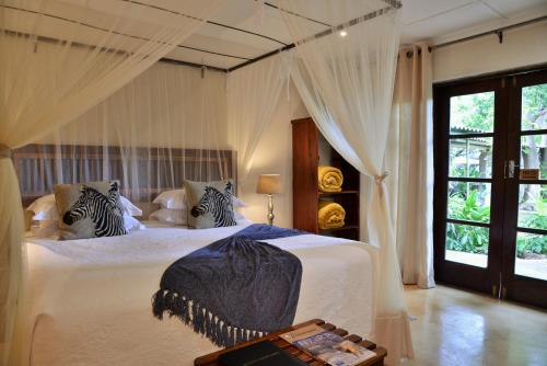A bed or beds in a room at Bayete Guest Lodge