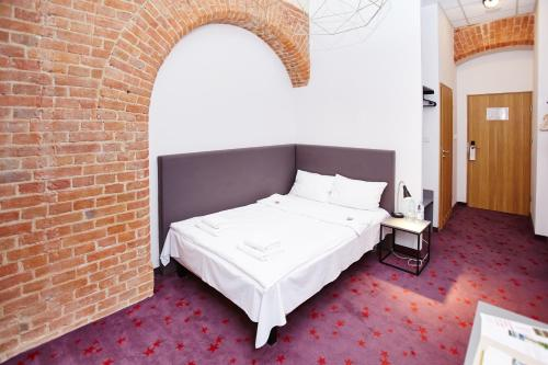A bed or beds in a room at Koszary Arche Hotel