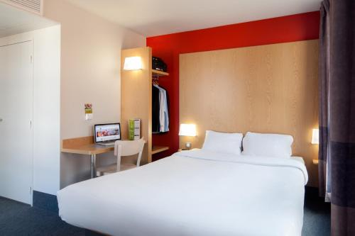 A bed or beds in a room at B&B Hôtel ORLY CHEVILLY Marché International