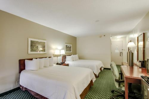 A bed or beds in a room at Ramada by Wyndham Dallas Love Field