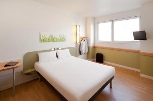 A bed or beds in a room at Ibis Budget Barcelona Sant Andreu De La Barca