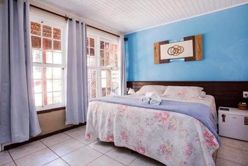 A bed or beds in a room at Pousada Palmeira Imperial