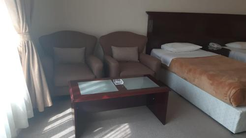A bed or beds in a room at Al Bustan Hotel
