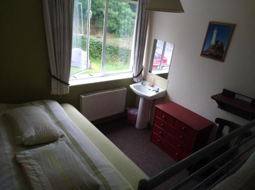 A bed or beds in a room at Dempseys Hostel