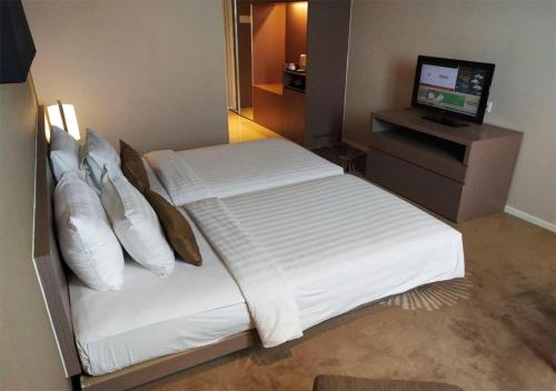 A bed or beds in a room at The Premiere Hotel Pekanbaru