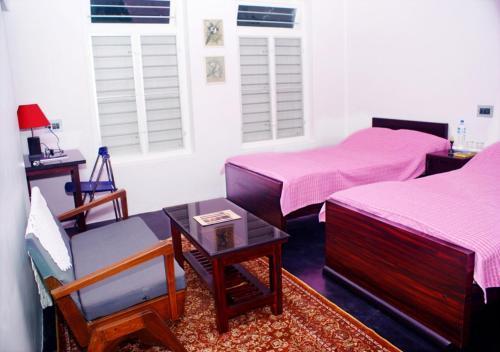 A bed or beds in a room at Sundara Mahal Homestay Wayanad