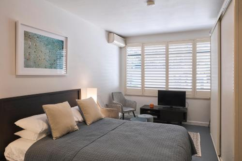 A bed or beds in a room at Ballantyne at Mosman - Serviced Apartments