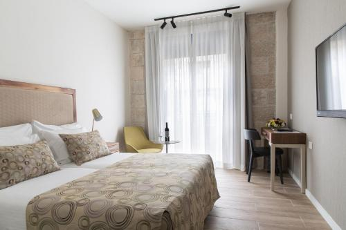 Een bed of bedden in een kamer bij Montefiore Hotel By Smart Hotels