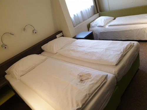 A bed or beds in a room at Behringers City Hotel Nürnberg