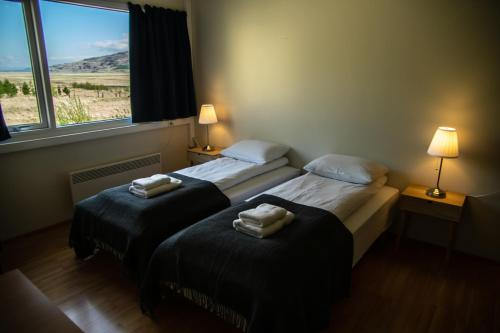 A bed or beds in a room at Hengifoss Guesthouse