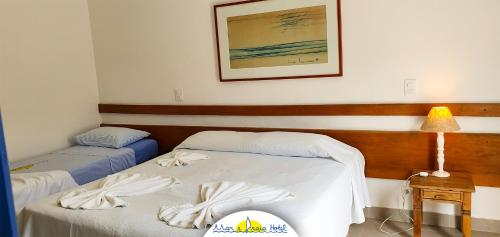A bed or beds in a room at Mar e Praia Hotel