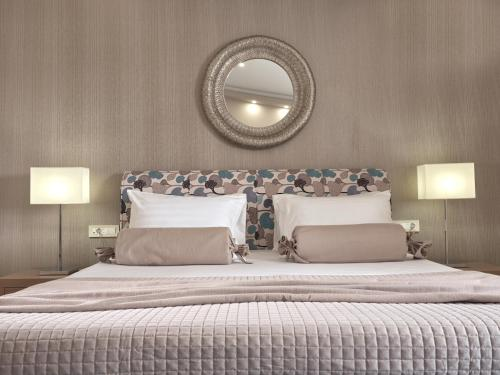 A bed or beds in a room at Koukounaria Hotel & Suites