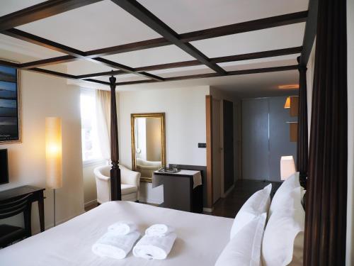 A bed or beds in a room at Hôtel de Carantec