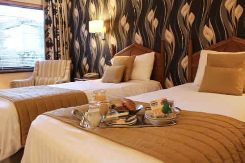 A bed or beds in a room at Crooklands Hotel