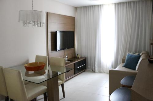 A television and/or entertainment centre at Porto do Sol Apartment