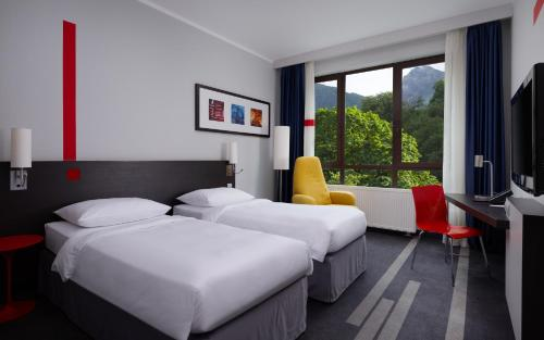 A bed or beds in a room at Park Inn by Radisson Rosa Khutor