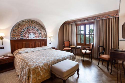 A bed or beds in a room at Grand Hotel Villa de France