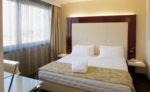 A bed or beds in a room at Grand Hotel Mattei