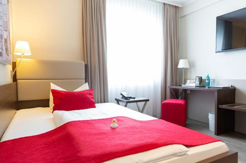 A bed or beds in a room at hotel bomonti Nürnberg West