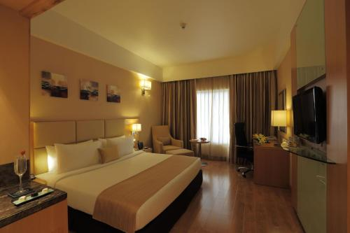 A bed or beds in a room at Country Inn & Suites By Radisson, Mysore