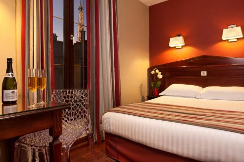 A bed or beds in a room at Hôtel Eiffel Rive Gauche