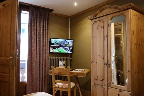 A television and/or entertainment center at Les Gourmets - Chalet Hotel