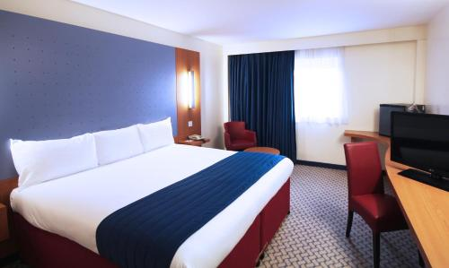 A bed or beds in a room at Ramada London North