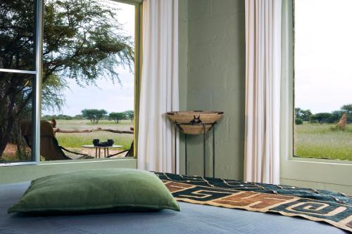 A bed or beds in a room at Okonjima Plains Camp