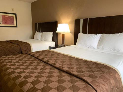 A bed or beds in a room at Travelodge by Wyndham Las Vegas Airport Near The Strip