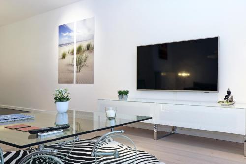 A television and/or entertainment center at Luxury Suite Koksijde 402 Adult only