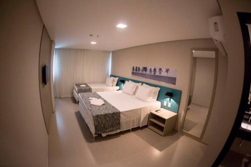 A bed or beds in a room at Acqua Suítes Maceió