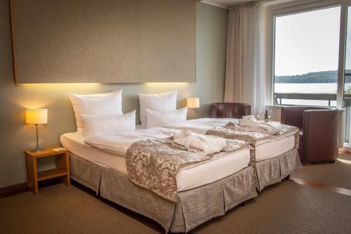 Ein Bett oder Betten in einem Zimmer der Unterkunft Seehotel Leoni