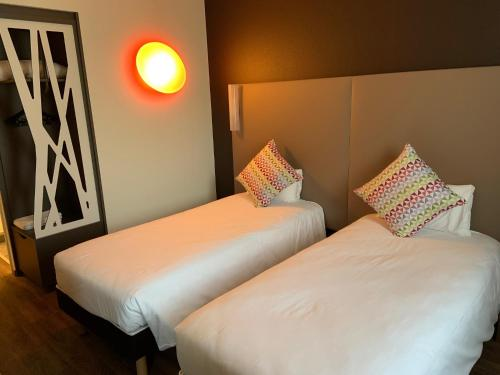 A bed or beds in a room at Campanile Saint Jean de Luz