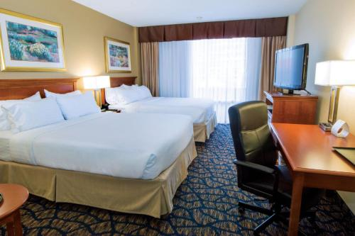 A bed or beds in a room at Holiday Inn Gainesville-University Center