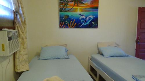 A bed or beds in a room at Hacienda Tropical Guest House