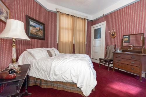A bed or beds in a room at Bisbee Grand Hotel