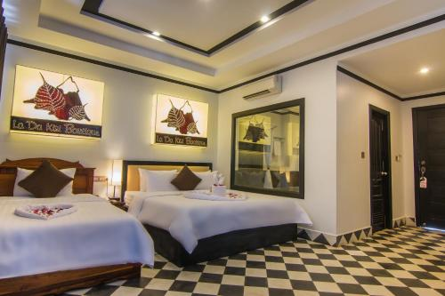 A bed or beds in a room at La Da Kiri Boutique Hotel