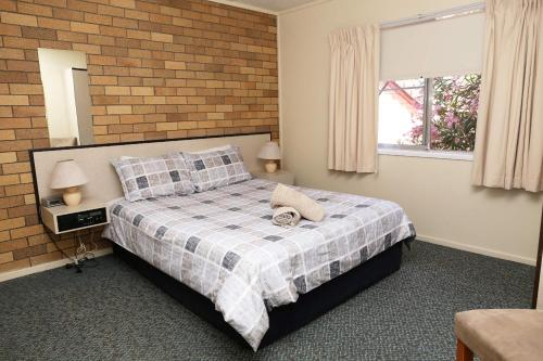 A bed or beds in a room at Westwood Motor Inn