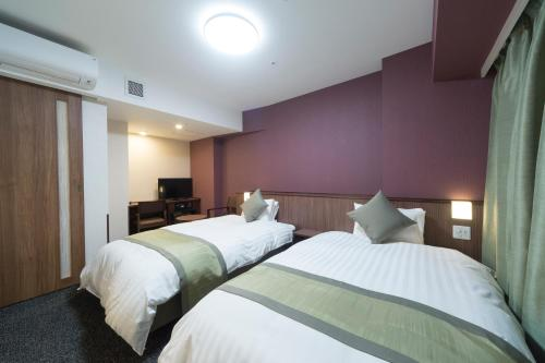 A bed or beds in a room at Myoujin-no-Yu Dormy Inn Premium Kanda