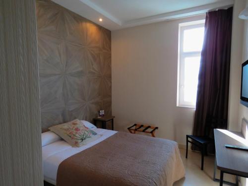 A bed or beds in a room at Hotel Ciudad de Fuenlabrada