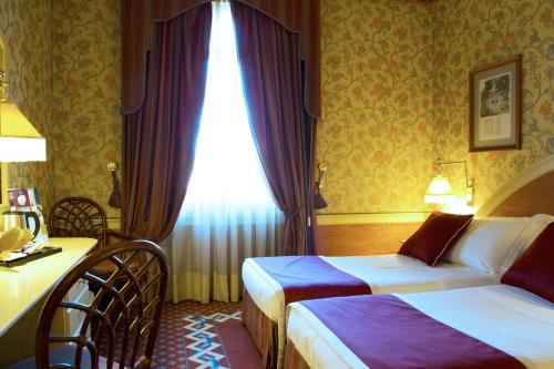 A bed or beds in a room at iH Hotels Milano Regency