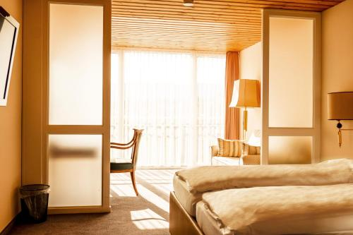 A bed or beds in a room at Hillsite Hotel Flims