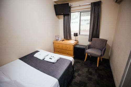 A bed or beds in a room at Shortland Budget Accommodation