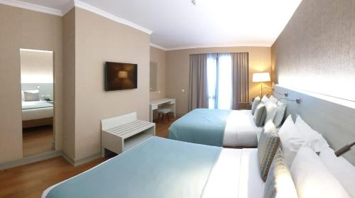 A bed or beds in a room at Enotel Lido Madeira - All Inclusive