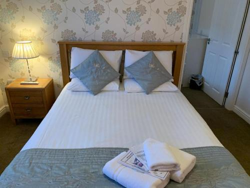 A bed or beds in a room at Lochside Guest House