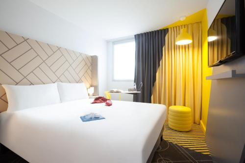 A bed or beds in a room at Ibis Styles Paris Massena Olympiades
